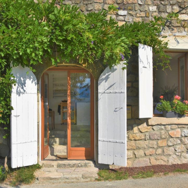 De openslaande deuren met witte luiken en een raam ernaast met geraniums ervoor