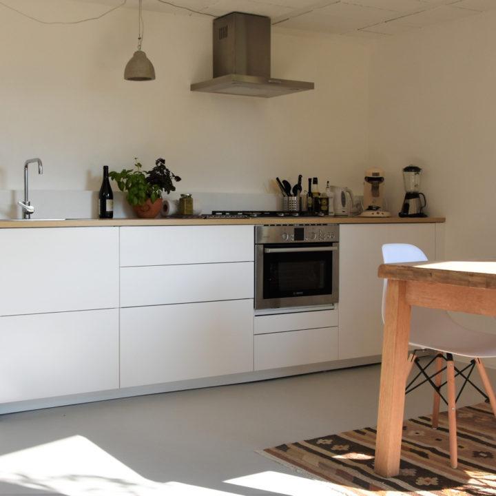 Moderne witte keuken met lades, een oven en afzuigkap. Houten tafel met wit kuipstoeltje