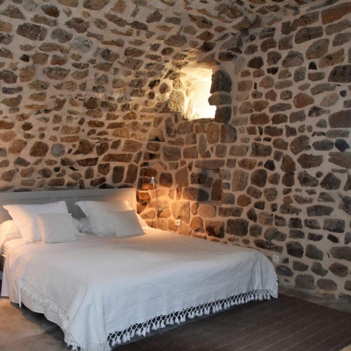 Een opgemaakt tweepersoons bed onder authentieke gewelven
