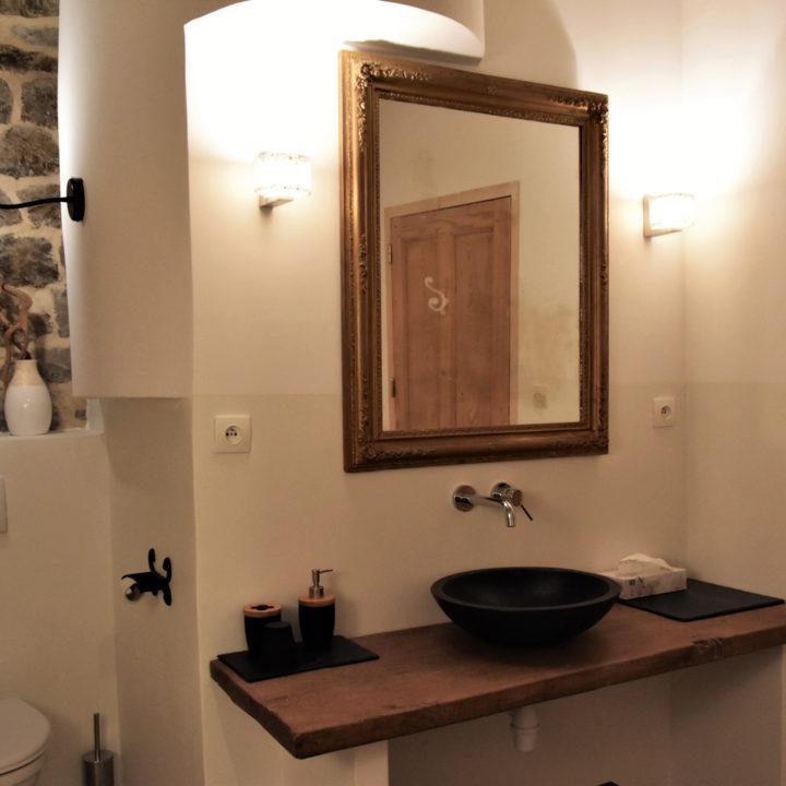Wastafel met houten blad, spiegel en lampjes ernaast