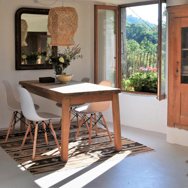 Houten tafel met witte kuipstoeltjes badend in het zonlicht