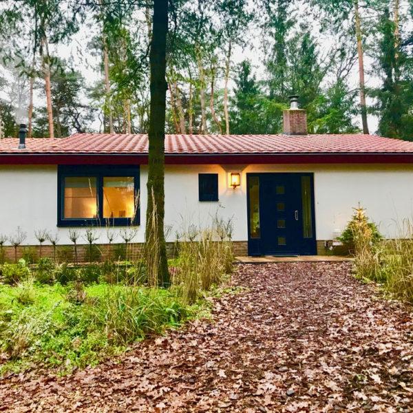 Witte bungalow in het bos met breed pad naar de voordeur