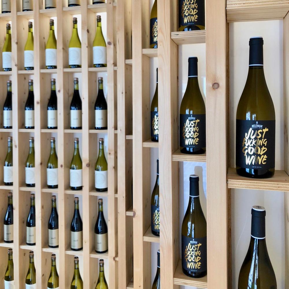 De wijnwinkel van Neleman in Zutphen, een rij wijnflessen op blank houten schappen