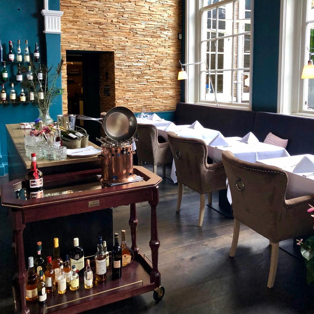 Gedekte tafels en een rek vol drank bij restaurant Chiel