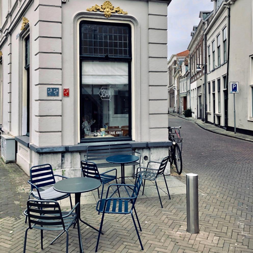 Smal hoekpandje met een terrasje ervoor met zwarte stoelen