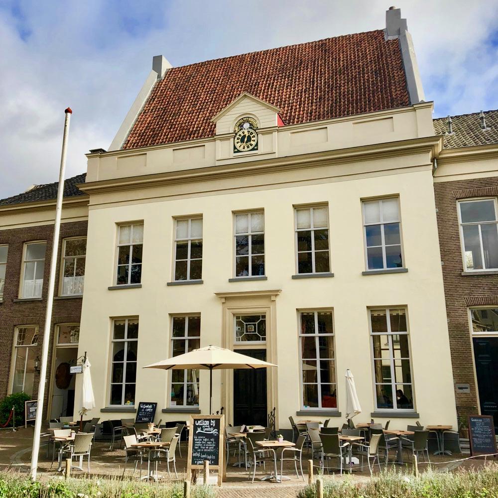 De zachtgele historische gevel van het Genietcafé in Zutphen, met een terras in de tuin