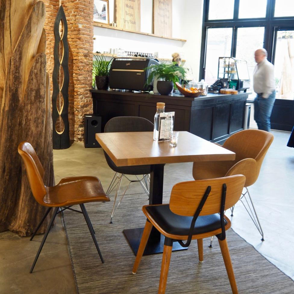 Koffie adres in een galerie. Een tafel met stoelen, hoge ramen en een toonbank