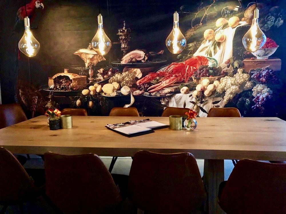 Houten tafel met aan de wand een werk van een van de Hollandse meesters