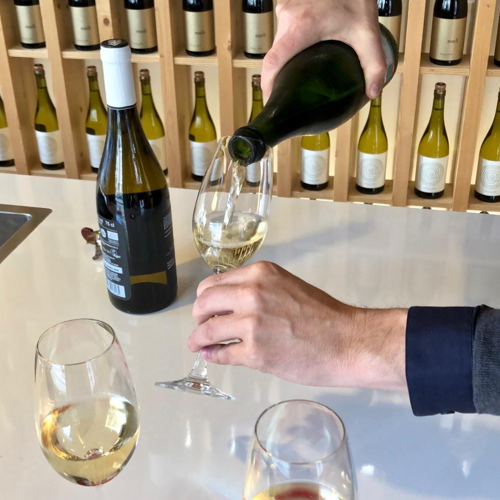 Wijn proeven bij Neleman, een man schenkt glazen wijn in