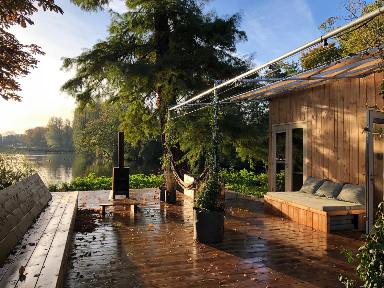Een houten vakantiehuis met groot terras, houtkachel buiten en een grote dennenboom