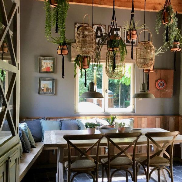 Woonkeuken met houten bank langs de wand, houten tafel en stoelen, planten in hangers aan het plafond