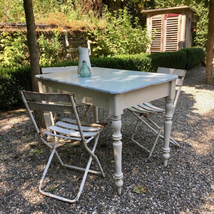 Brocante tafel in de tuin, met witte bistro stoelen