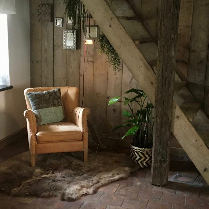 Hoekje onder de trap met leren fauteuil, houten trap, bont op de grond