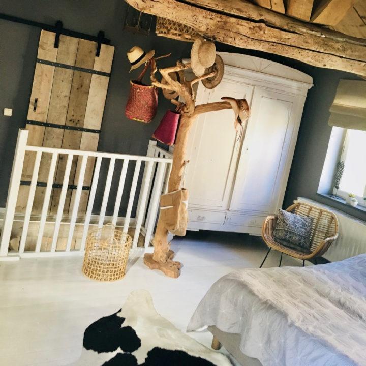 Slaapkamer met witte brocante kast en boomstam met hoedjes eraan
