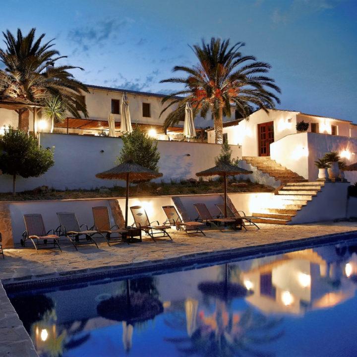 Zwembad bij avondlucht met Casa en palmbomen