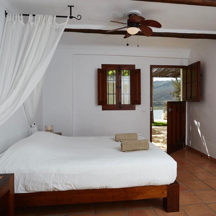 Tweepersoons bed met klamboe en deur naar buiten