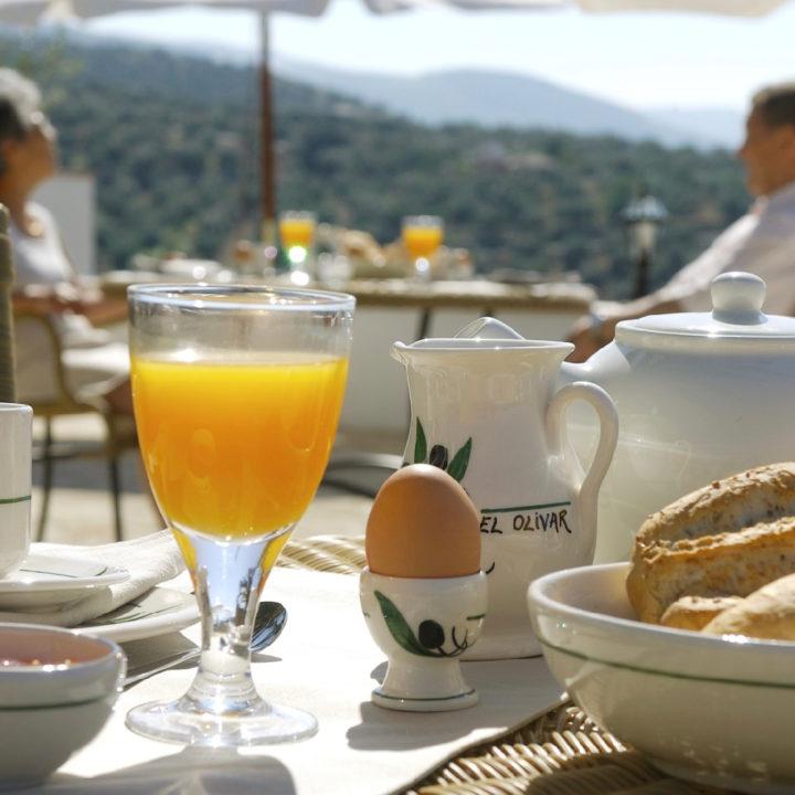 Ontbijt met jus d'orange, eitje en broodjes in de zon
