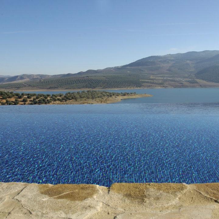 Infinity pool waarbij het lijkt alsof het water van het zwembad overgaat in het meer