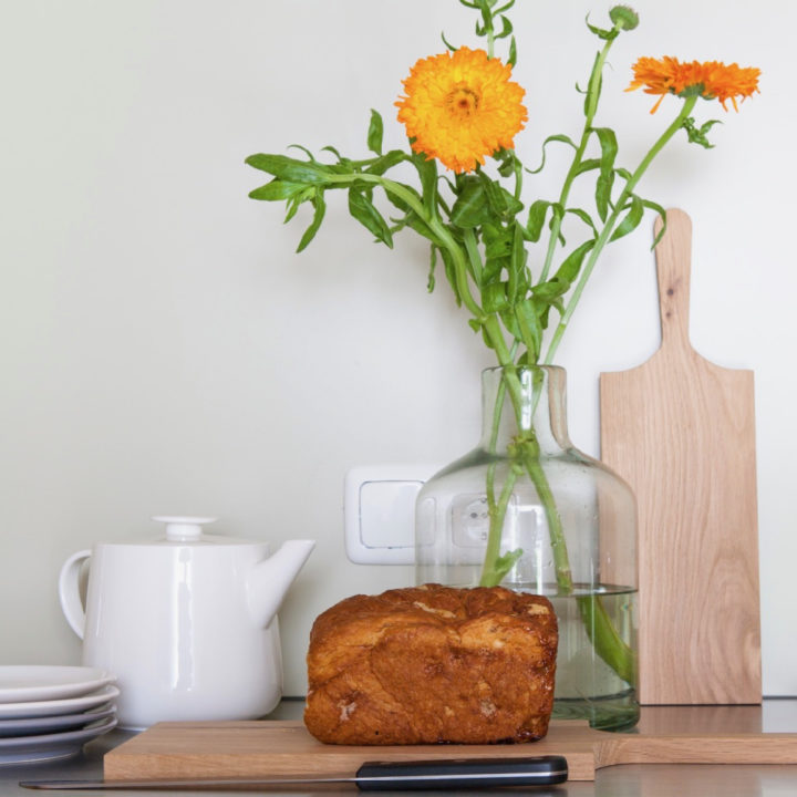 Oranje bloemen in vaas, Fries suikerbrood en houten plank