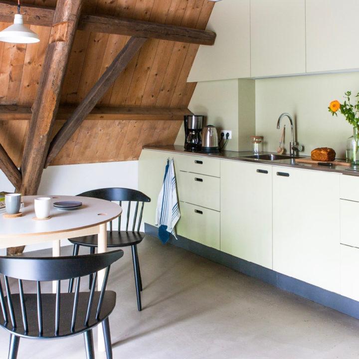Witte keuken onder schuin houten dak, ronde eettafel met zwarte stoelen
