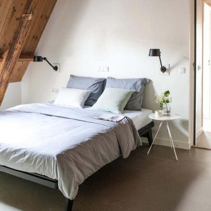 Tweepersoons bed met grijs bedlinnen in appartement BOS