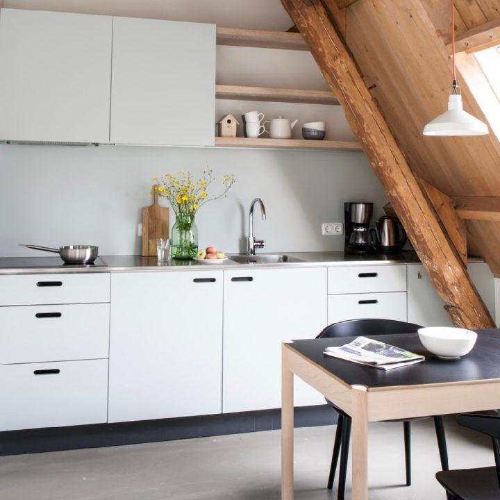 Keukenblok en eettafel, onder schuine houten gebinten