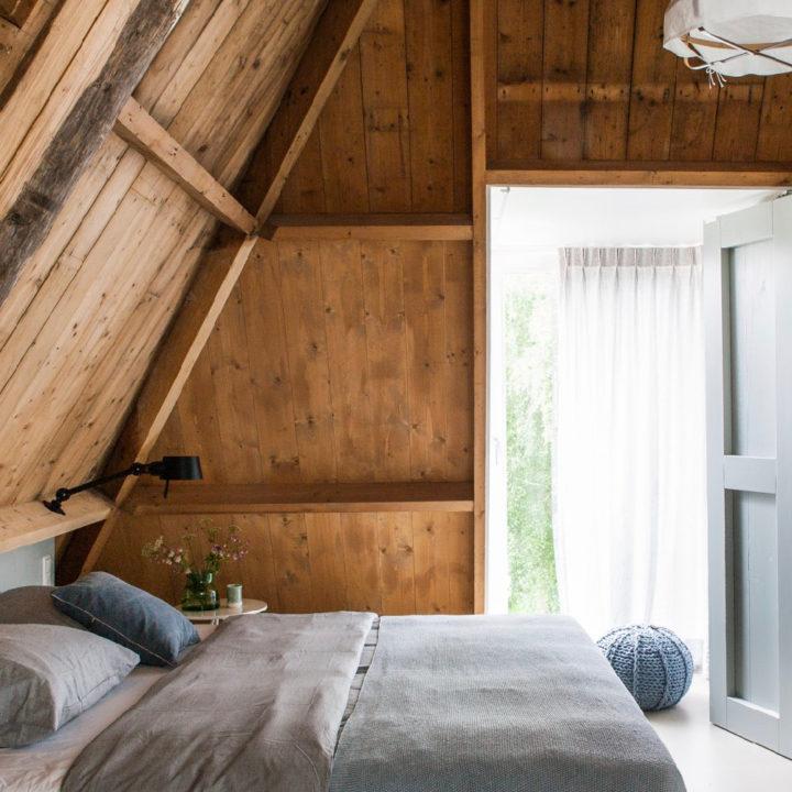 Tweepersoons bed in appartement water, met grijs linnen goed en poef op grond voor het raam
