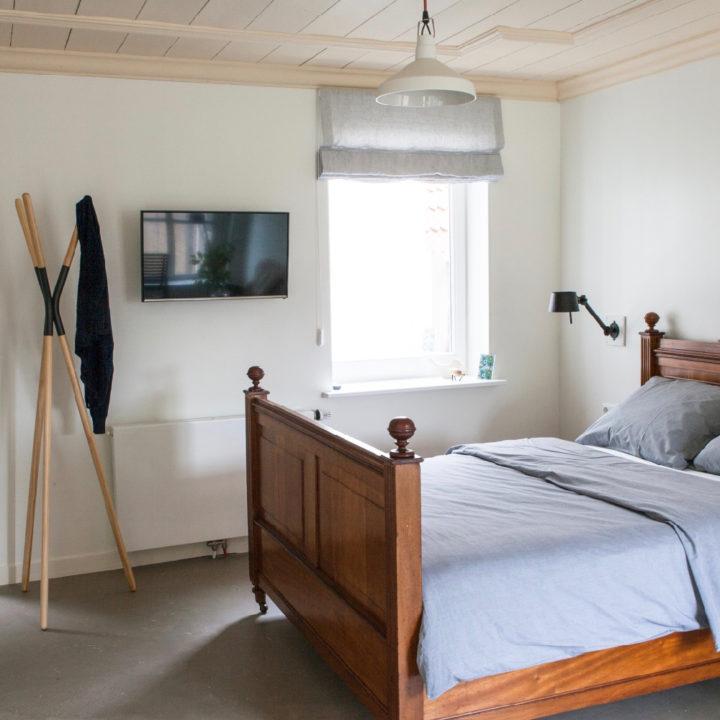 Opgemaakt antiek houten bed met grijs bedlinnen, TV aan de muur