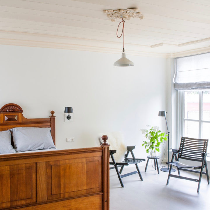 Opgemaakt antiek bed en zwarte stoeltjes voor het raam