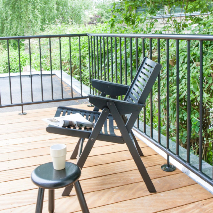 Balkon met zwarte stoel en zwart krukje