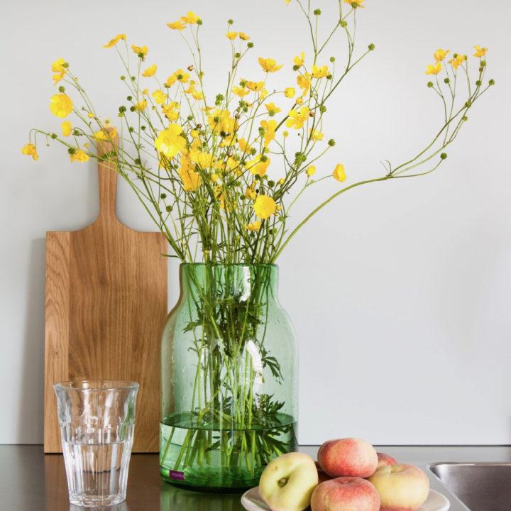 Bloemen in vaas op aanrecht en schaal met wilde perzikken