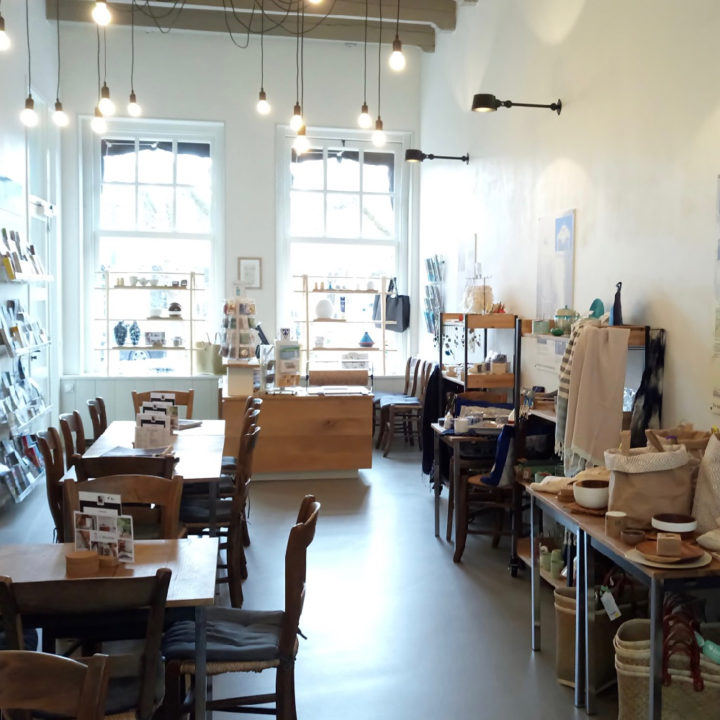 Tafels en stoelen, wanden met woonaccessoires, grote ramen