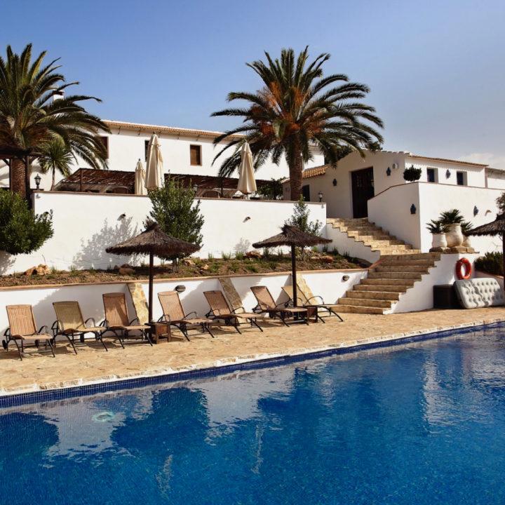 Zwembad met ligstoelen, palmbomen en Spaanse casa