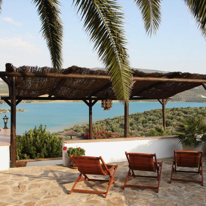 Ligstoelen met zicht op meer, tussen de palmbladeren