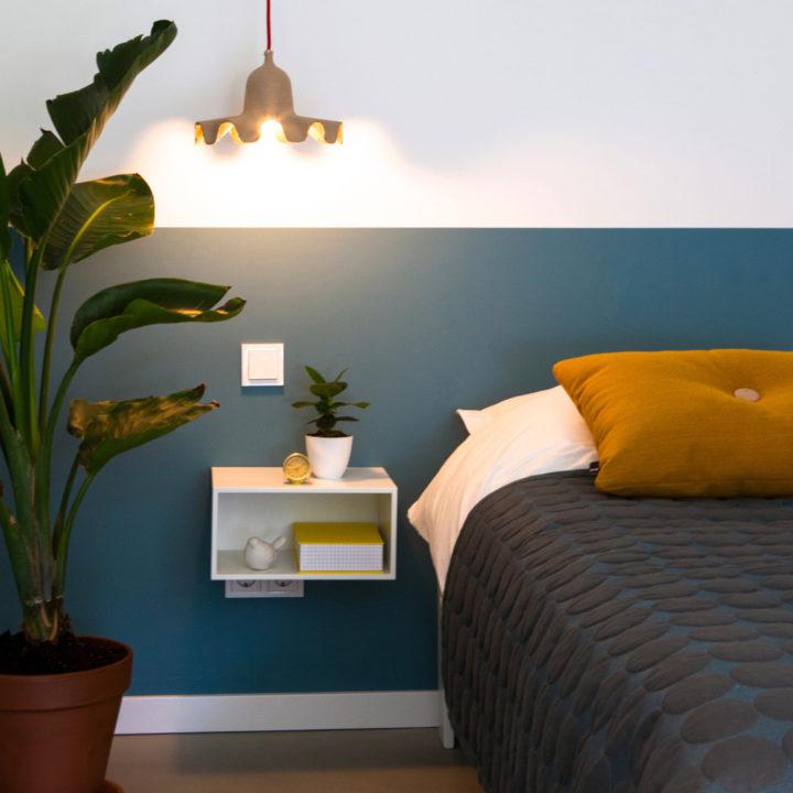Close up van slaapkamer met tweepersoons bed, okergeel kussen en blauw geschilderde lambrisering
