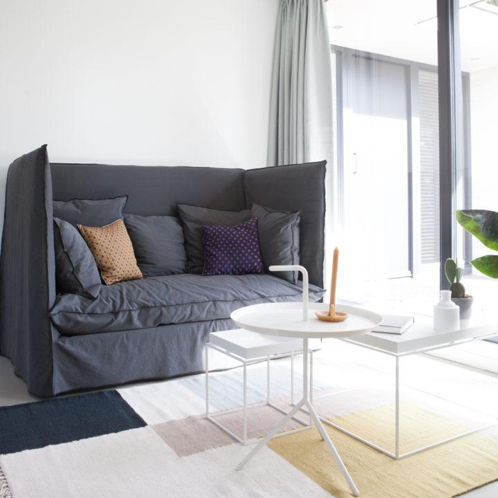 Zitbank met witte salontafels en groot raam