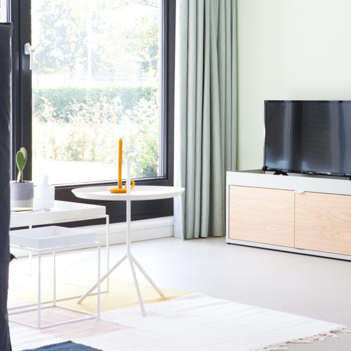 Zithoek met TV, wit salontafeltje en groot raam met lichtgrijze gordijnen