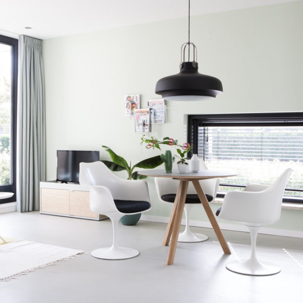 Ronde houten eettafel met witte designstoelen