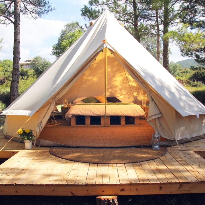 Openstaande bell tent met opgemaakt bed
