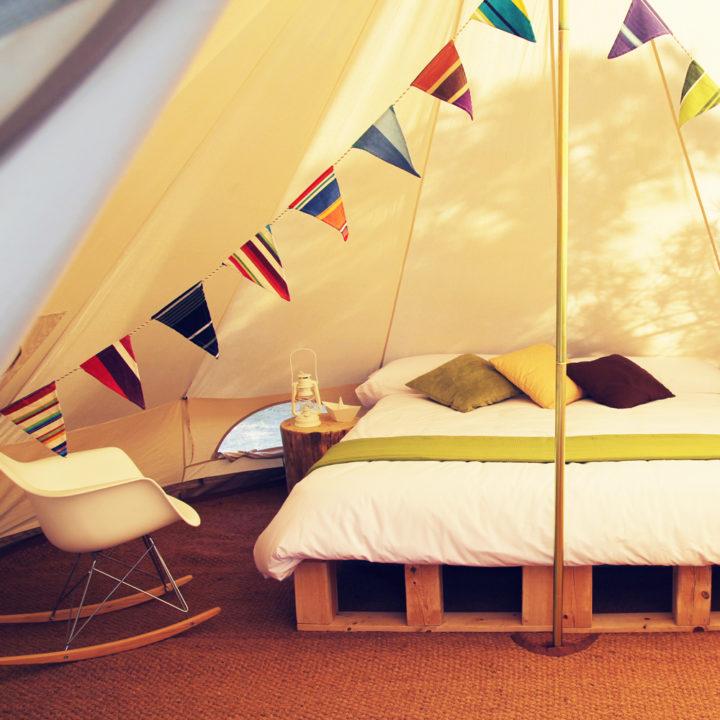 Opgemaakt bed op pallets en vlaggenlijn in bell tent