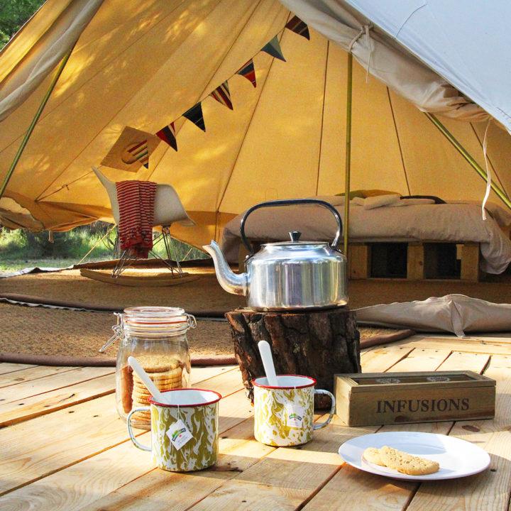 Ketel en mokken op houten vlonders met openstaande witte bell tent