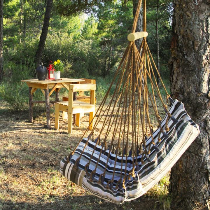 Hangstoel aan boom en houten tafel en stoel op bosgrond