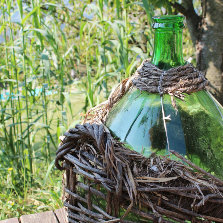 Grote groene wijnfles met rieten omhulsel
