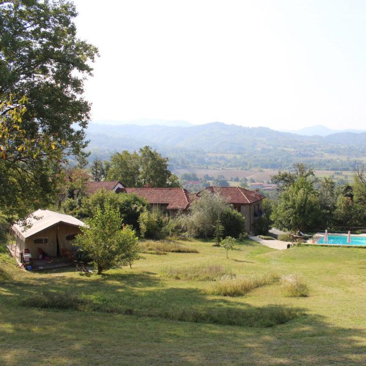 Een safaritent op een grasveld met zwembad, met zicht over de heuvels
