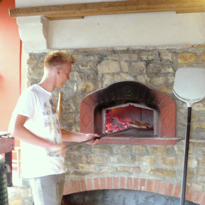 Een jongeman schuift een pizza in hout gestookte pizzaoven