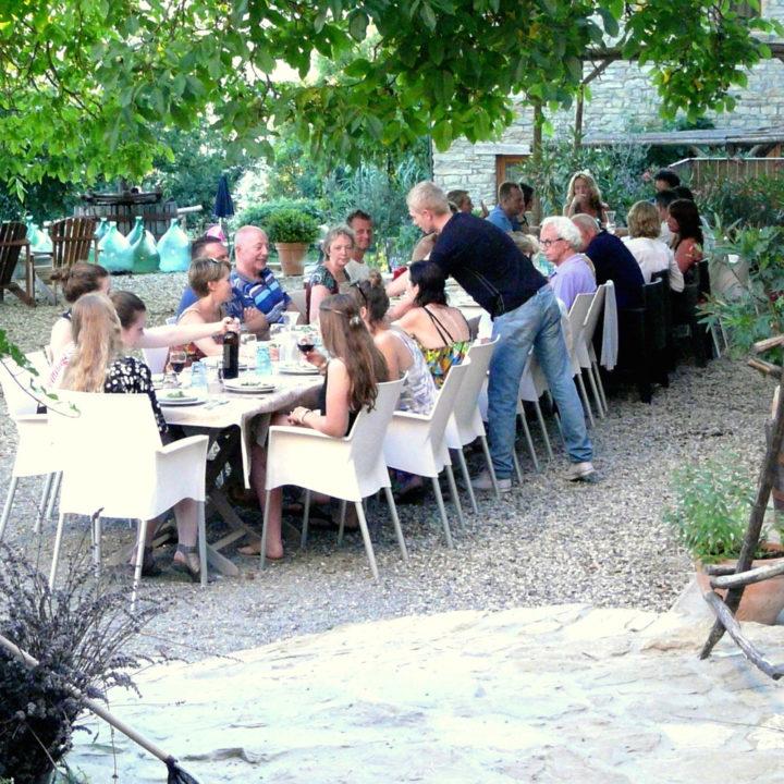 Lange tafels met vakantiegasten dineren samen