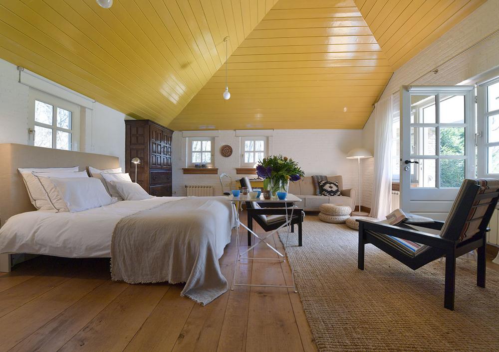 Tweepersoons bed met zithoek, openslaande deur en geel houten plafond