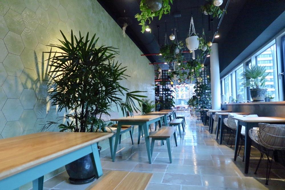 Houten tafels met blauw metalen frame en banken met grote planten ertussen bij restaurant picnic