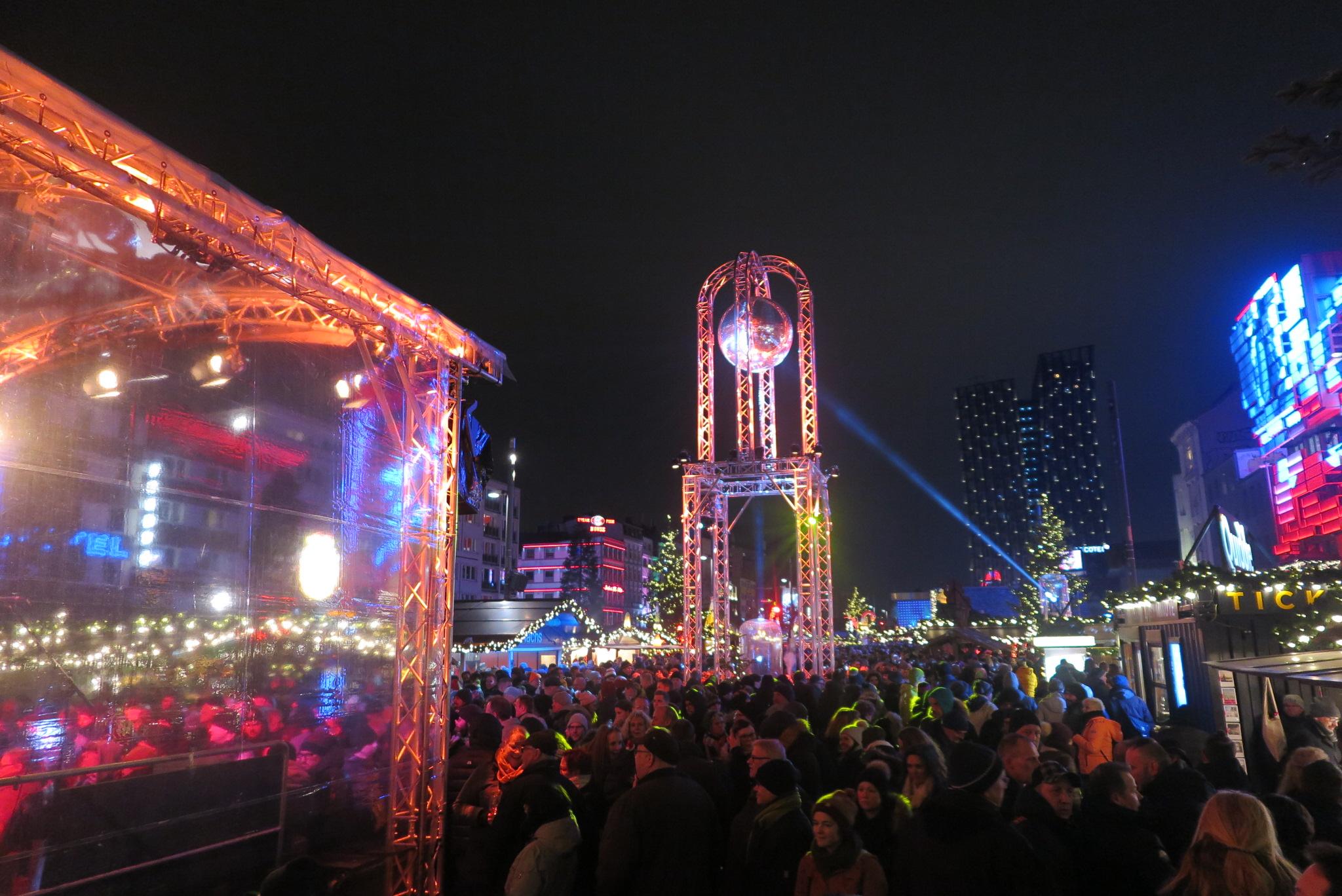 Een kerstmarkt met tientallen lampjes, in het donker