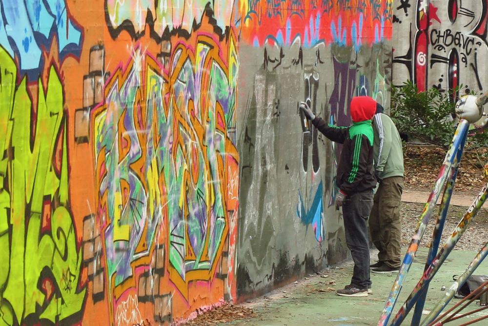 Street art kunstenaars aan het werk op een muur in Hamburg